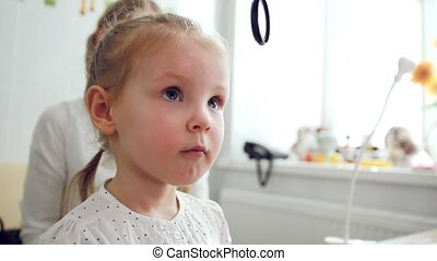 Cute child in ophthalmology clinic - optometrist diagnosis...