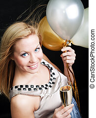 smiling woman holding new year's champagne and balloons over...