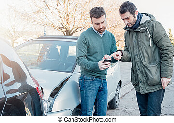 Two man using mobile phone after a car crash