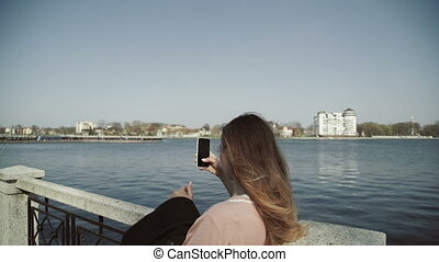Young beautiful woman taking pictures with her smartphone in the city park near the lake