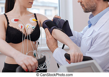 Busy careful doctor putting on a blood pressure cuff
