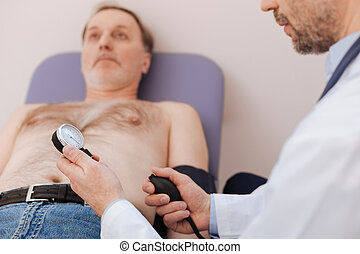 Competent capable medical worker reading blood pressure