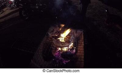 Roast pork on a charcoal stove.