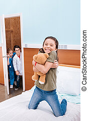 girl hugging teddy bear while boy doctor and girl nurse...