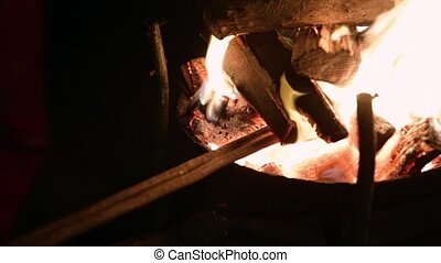 Man takes a heated metal billet out of the furnace - Blanket...