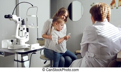 Ophthalmologist in clinic explains diagnosis about girl's...