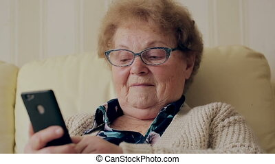 Old woman using new smartphone. - Old woman using new...