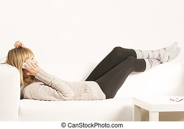 Woman with cellphone laying on sofa