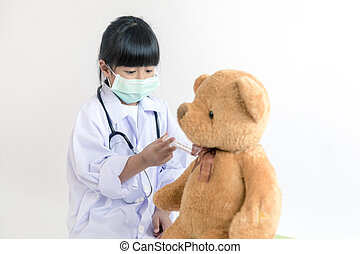 child playing doctor with stethoscope and teddy bear