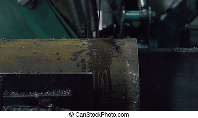 Band saw cutting metal tube with water jet cooling - Close...