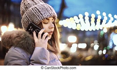 Young Asian woman talking on smart phone, sitting on a wooden bench in the park of the city at night