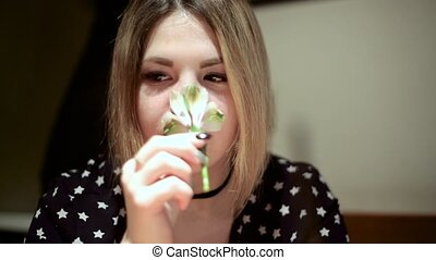 Asian girl woman sniffing a small white flower
