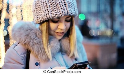 Asian girl is typing on your smartphone. Background of yellow garlands. Smiling, happy, beautiful.