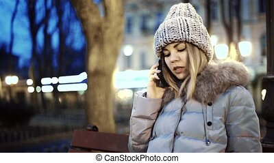 Young woman talking on smart phone, sitting on a wooden bench in the park of the city at night