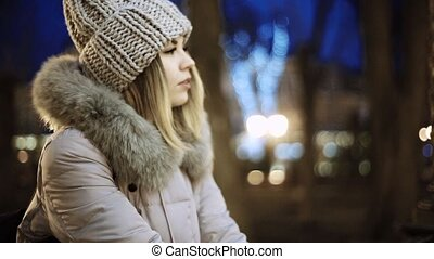 A young Asian girl looks in a park the city at night on the background lights. Smiling.On both sides