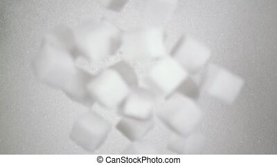 Sugar cubes fall down on sugar. Slow mo, top view