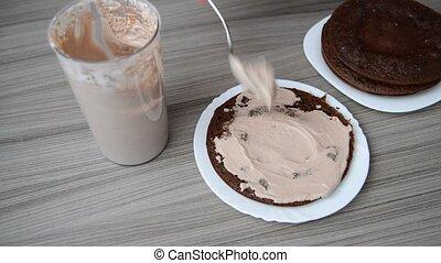 Woman smears sponge cake with cream - Woman smears a sponge...
