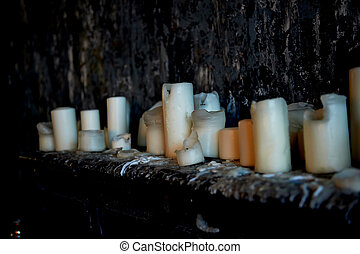 Candle stand on a dark surface against a dark wall, all in...