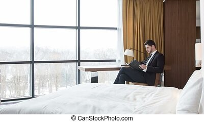 Serious businessman sitting in his hotel room - Time to...