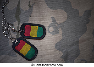 army blank, dog tag with flag of guinea on the khaki texture...