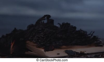 Burning book on the sand at coast HD storm clouds on...