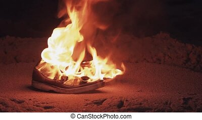 Burning boots on the sand at coast strong bright flame...