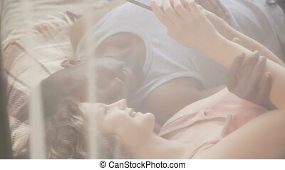 Young multiethnic couple lying on bed and use smartphone....