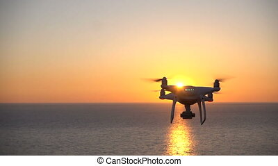 Drone flies over the sea toward the sunset, slow motion