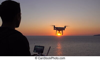 Drone flies over the sea toward the sunset, operator...