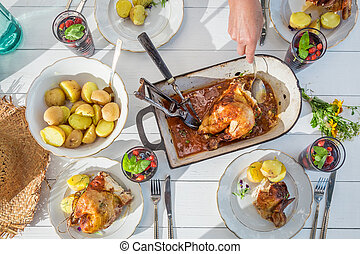 Fresh dinner with chicken and potatoes served in the garden