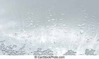 Springtime snowfall accumulates against a window pane -...