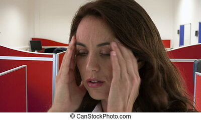 Young woman having headache in the office