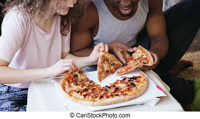 Hungry multiethnic couple eating pizza. Man and woman feeds...