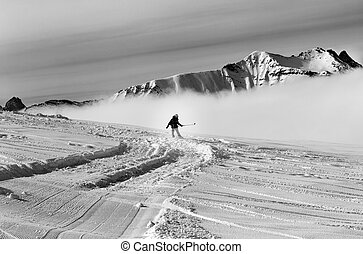 Snowboarder downhill on off-piste slope with newly-fallen...