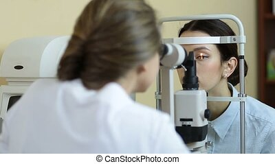 Optometrist examining female patient on slit lamp - Back...