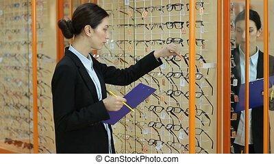 Pretty female optician revising glasses in optics -...