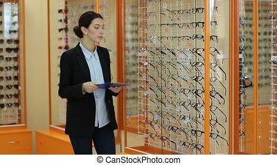 Optician checking showcase with glasses in store - Confident...