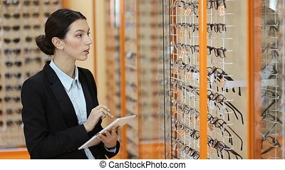 Attractive optician working with tablet in optics -...