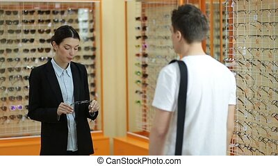 Female optician showing glasses to man at optics - Adorable...