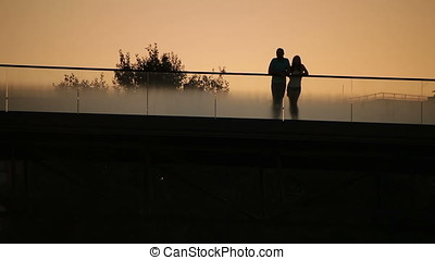 Silhouette of Couple at Dusk on Bridge - Silhouette of...