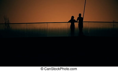 Lovers Couple Silhouette at Dusk on Bridge - Lovers couple...