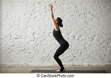 Young yogi attractive woman in Chair pose, white loft background