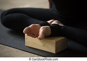Closeup of female feet in Butterfly pose with block, studio...