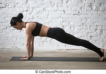 Young yogi attractive woman in Plank pose, white loft...