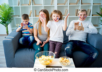 Happy young family watching television