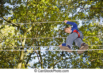 climbing - a boy climbing in adventure park