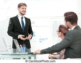 Successful business man in suit at the office leading a group