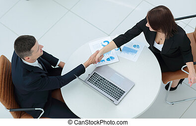Confident business partners shaking hands and smiling -...
