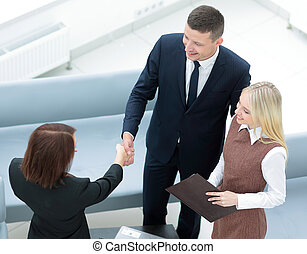 Confident business partners shaking hands and smiling. Top...