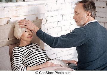 Senior man measuring temperature of his wife